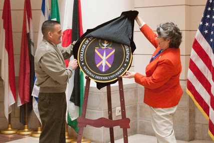 General Padilla and Chancellor Hamby remove the cover to reveal the new College of Information and Cyberspace seal.